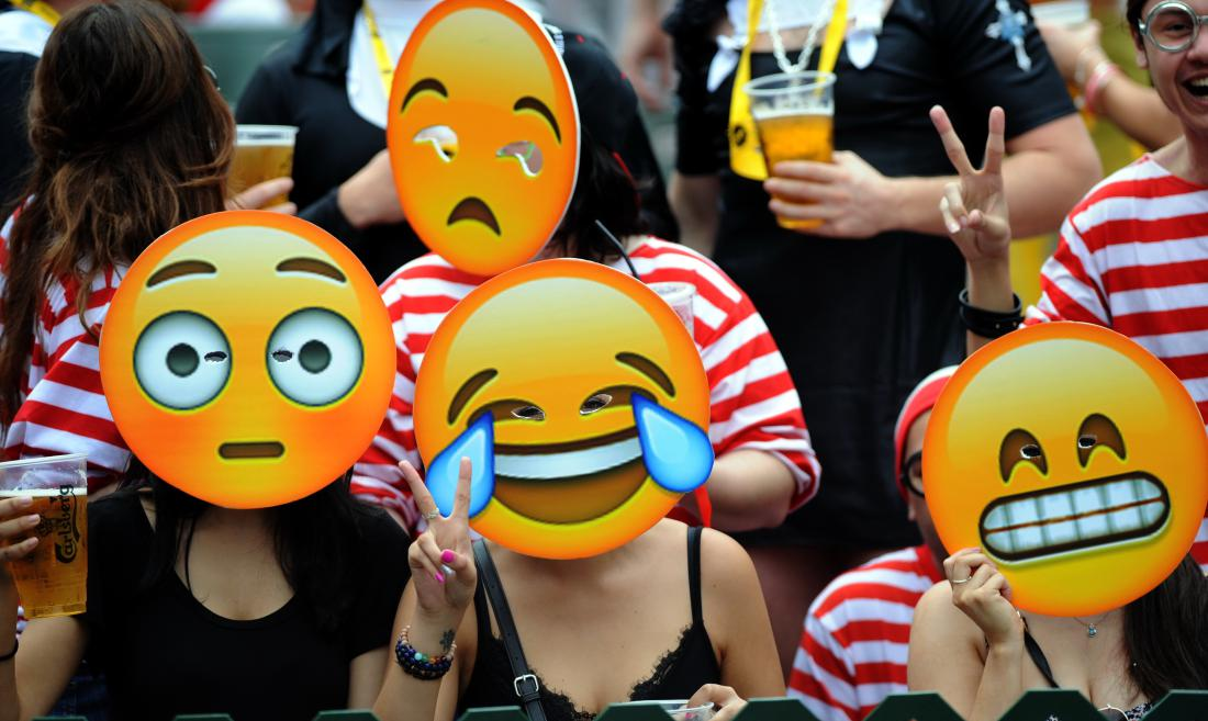 Fans wearing emoji masks watch a rugby match of the Hong Kong Seven 2015 in Hong Kong, China, 28 March 2015.  At the Hong Kong Rugby Sevens 120,000 people turn up, a lot of beer is drunk, colorful costumes are flaunted and Fiji normally wins. This year was the 40th anniversary of the tournament and the event followed the script. Fiji beat New Zealand 33-19 in the final to win for a record 15th time, and the crowd barely noticed. One of the loudest cheers of the day came when Zimbabwe scored a try against Russia. Neither nation is known for its rugby. There were also noisy jeers when Hong Kong Chief Executive Leung Chun-ying was announced at the prize giving cermony. The rugby forms a backdrop in Hong Kong to the crowd, the reveling thousands who turn up in coordinated costumes to party and drink beer, sold in one-liter plastic cups. Long lines form for the south stand of the Hong Kong Stadium, the most raucous spot to sit or stand. Long lines then also form for the bathrooms. Many people in the stadium weren't watching the rugby, instead swiveling away from the pitch to look at the people in the crowd behind them as they danced and threw rugby balls and glasses of beer at each other.